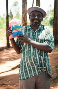 Farmer holding bag of maize.