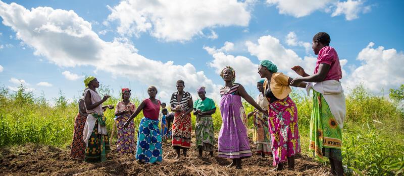 Women stand in field.
